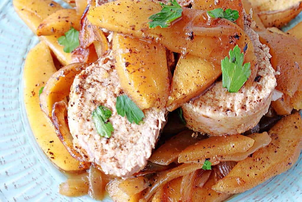 A super closeup of slices of Skillet Pork Tenderloin topped with cinnamon apples on a blue plate with a parsley garnish.