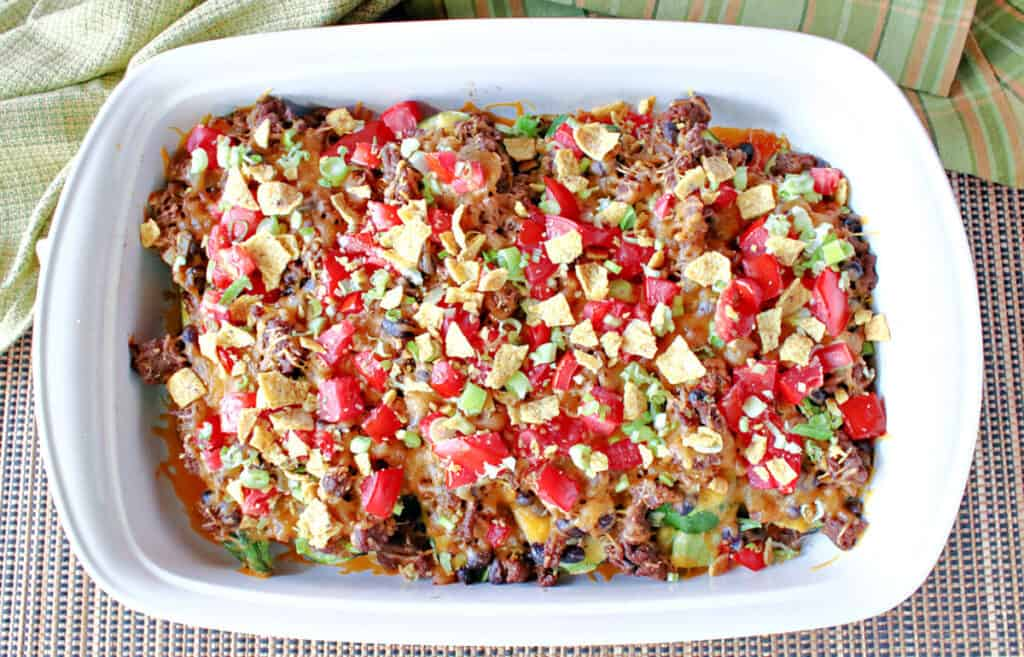 A direct overhead photo of a white casserole dish filled with Taco-Filled Zucchini Boats with tomatoes, green onions, ground beef and cheese.