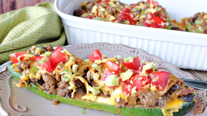A Taco-Filled Zucchini Boat filled with ground beef, tomatoes, cheese, and beans in the foreground with a casserole dish in the background.
