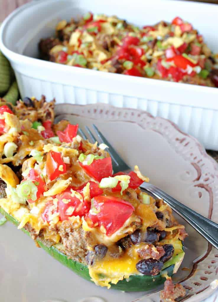 A closeup vertical photo of Taco Filled Zucchini Boats on a plate with a casserole dish in the background.