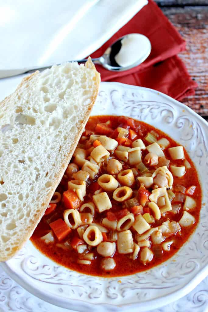A bowl of hearty Tuscan Pasta Soup in a white bowl with napkins and a spoon in the background.