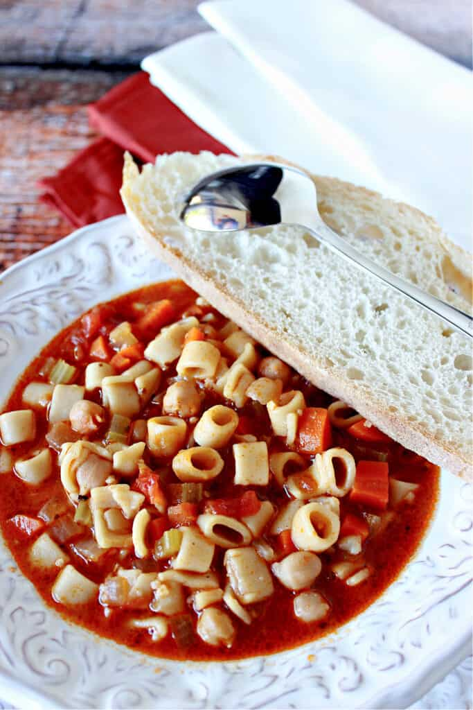 An overhead vertical closeup of a white bowl filled with Tuscan Pasta Soup with a spoon and a slice of bread on the side.