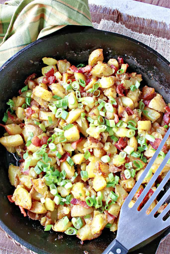 A vertical overhead photo of German Fried Potatoes in a cast iron skillet along with scallions for garnish.