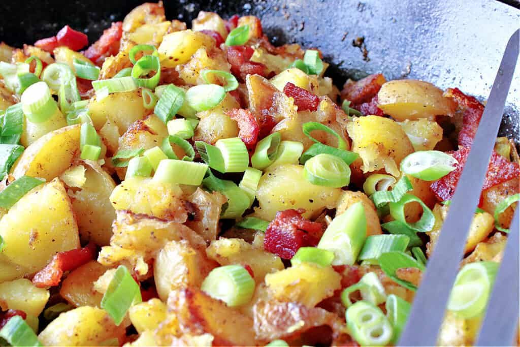 A horizontal closeup of German Fried Potatoes in a cast iron skillet along with bacon and scallions.
