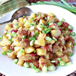 A white bowl filled with German Fried Potatoes along with scallions and a spoon.