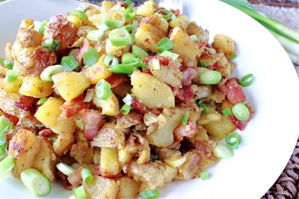 An offset horizontal photo of German Fried Potatoes in a white bowl topped with bacon and scallions.