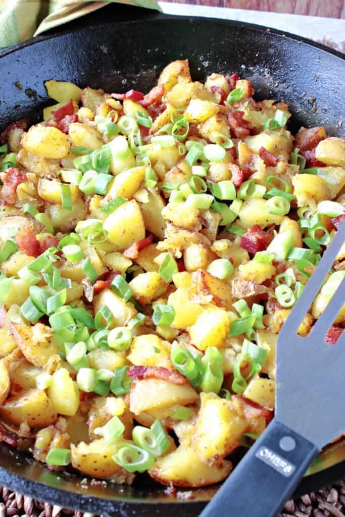 A vertical closeup of a cast iron skillet filled with German Fried Potatoes along with bacon and scallions.