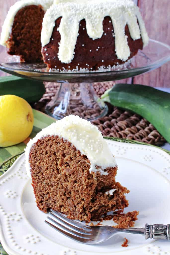 A vertical closeup of a slice of Gingerbread Bundt Cake with Zucchini on a plate with an entire cake on a cake stand in the background.