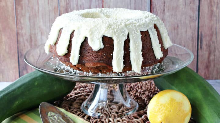 A Gingerbread Bundt Cake wit Zucchini on a cake stand with a lemon and zucchini on the table.