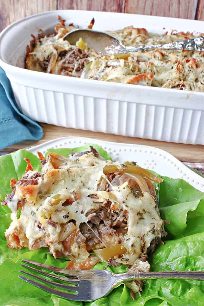 A vertical closeup of a serving of Italian Beef and Gravy Bread Pudding on a plate with lettuce along with a casserole dish filled with Italian Bread Pudding in the background.
