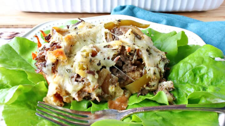 A serving of Savory Italian Beef Bread Pudding on a bed of lettuce with a fork.