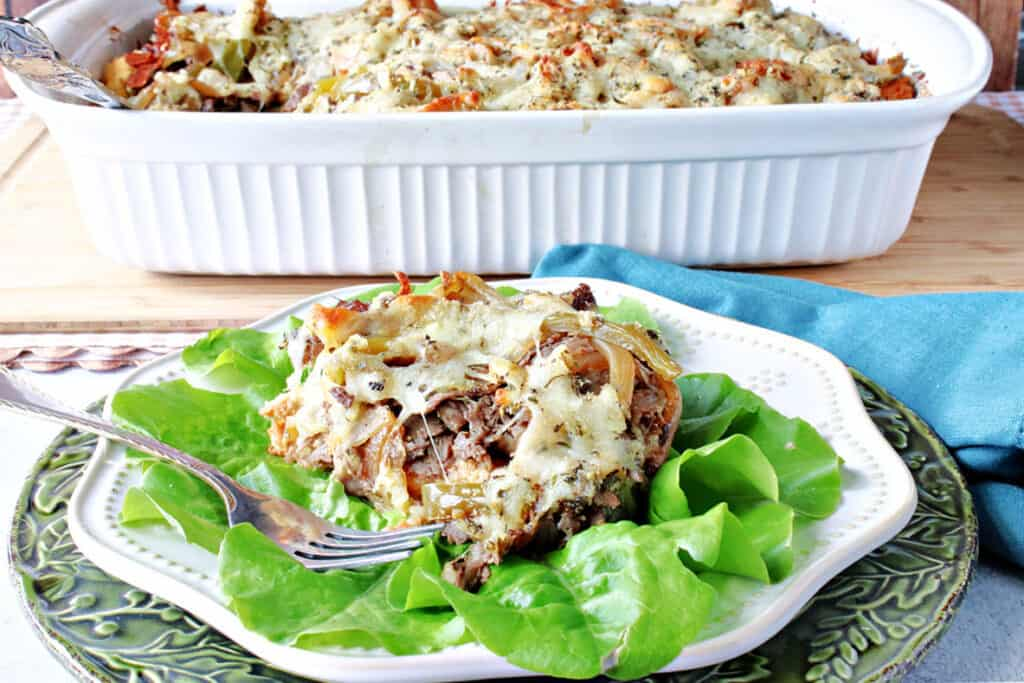 A plate of savory Italian Beef Bread Pudding in the forefront along with a casserole dish filled with the casserole in the background along with a blue napkin.