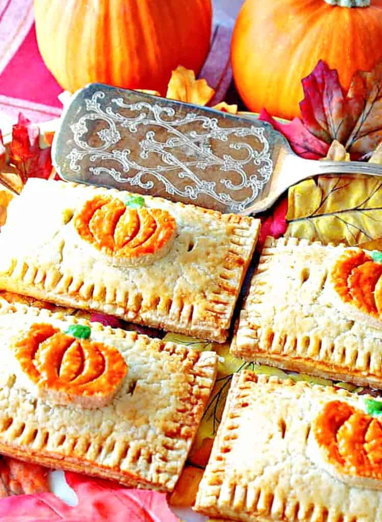 A vertical overhead closeup photo of 4 Pumpkin Hand Pies on a platter with a silver serving spatula and autumn leaves.
