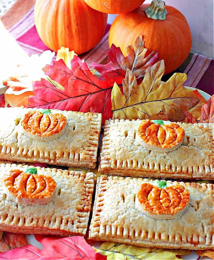 A vertical closeup image of four Pumpkin Hand Pies with pumpkin pie crust embellishments on a platter with autumn leaves and pumpkins in the background.