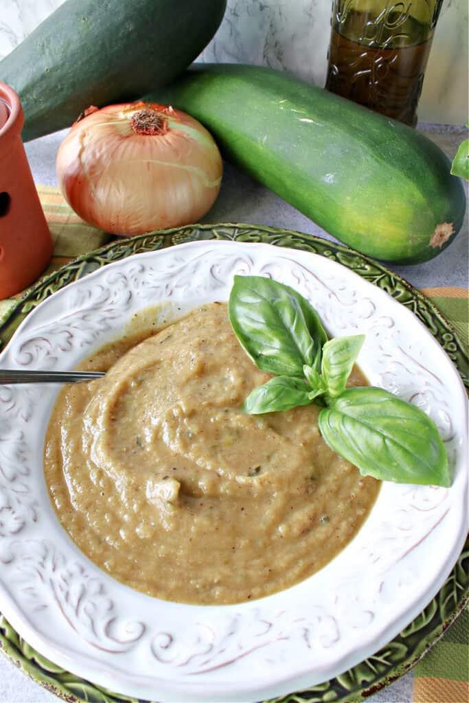 A vertical overhead closeup of a creamy bowl of Roasted Garlic and Zucchini Soup with fresh basil as garnish with a spoon in the bowl.