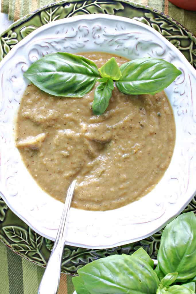 A vertical closeup overhead photo of a full bowl of Roasted Garlic and Zucchini Soup with fresh basil leaves as garnish.