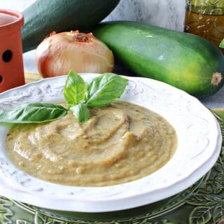 A white bowl filled with Roasted Garlic and Zucchini Soup along with some fresh basil and a spoon on the side.