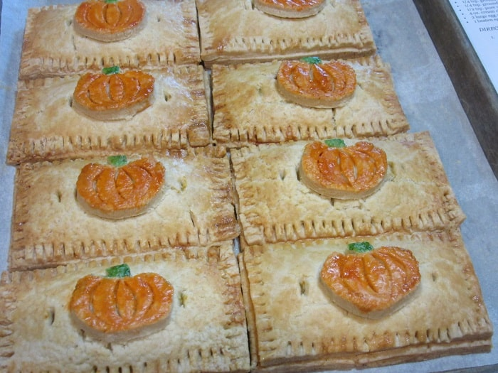 A horizontal photo of eight Pumpkin Hand Pies on a baking sheet with painted pie crust embellished pumpkins on top.