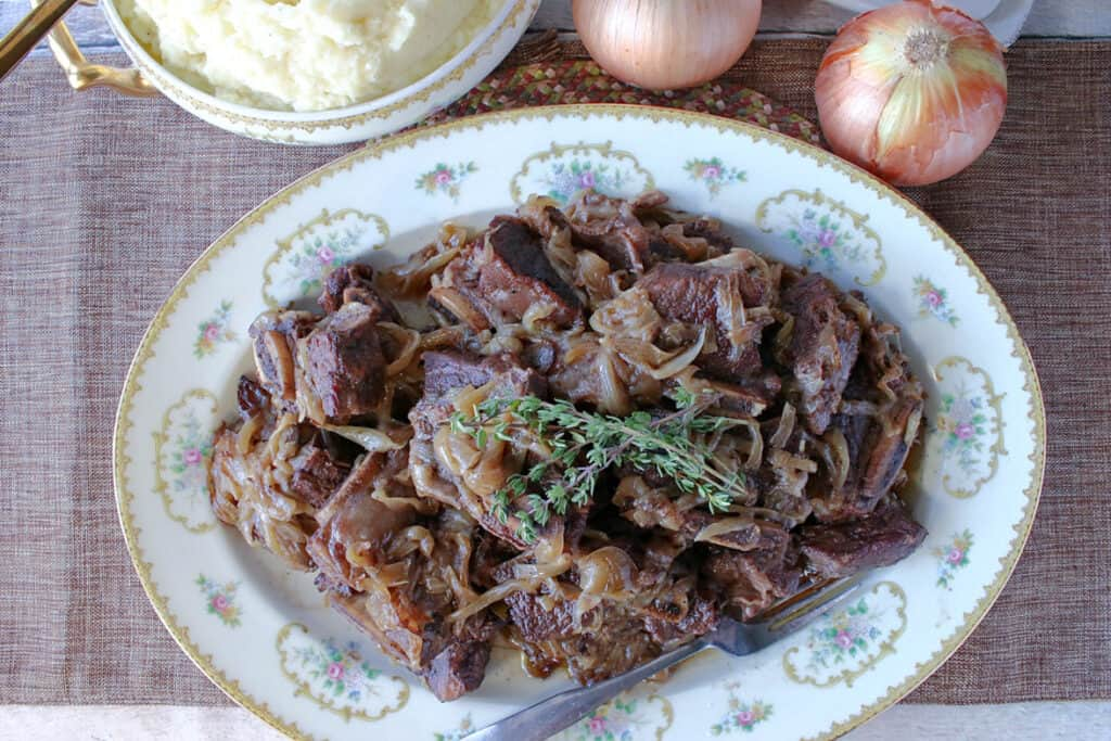 A horizontal overhead photo of a platter filled with French Onion Short Ribs with caramelized onions, fresh thyme and a fork.