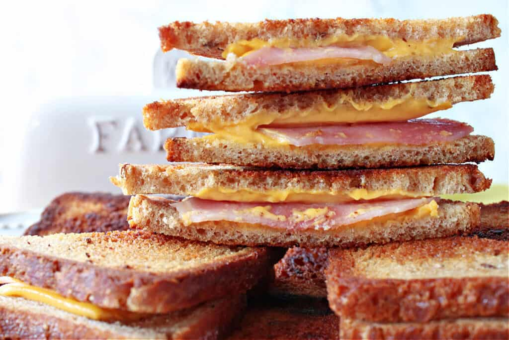 A closeup of a stack of cut Grilled Ham and Cheese Appetizers on mini cocktail bread with melted cheese and ham inside.