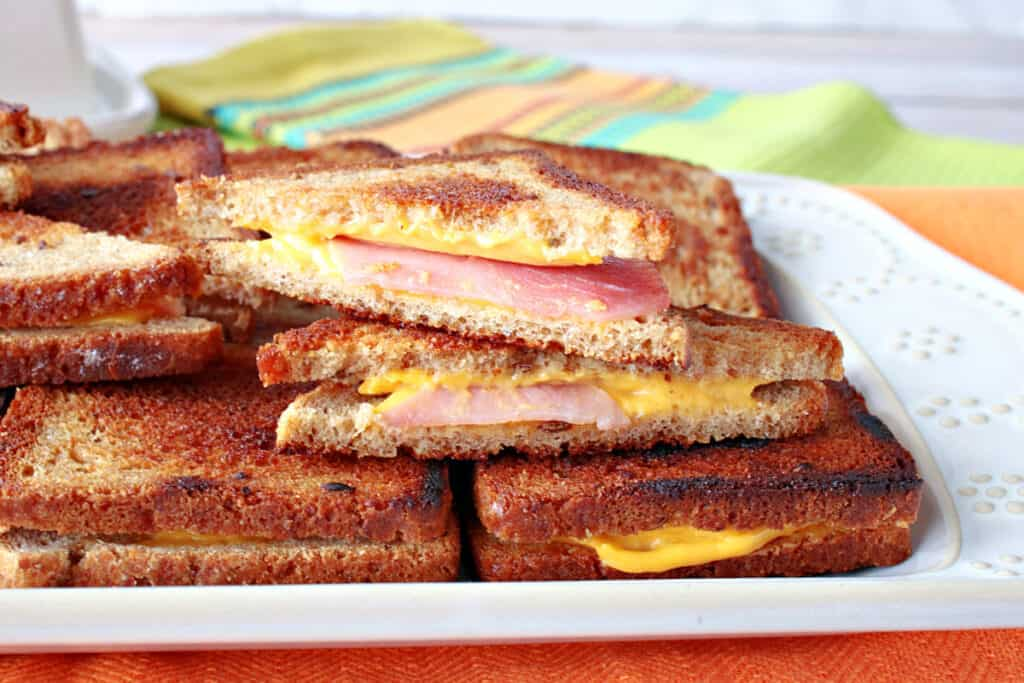 A horizontal close up of a platter of mini Grilled Ham and Cheese Appetizer sandwiches with melted cheese and ham.