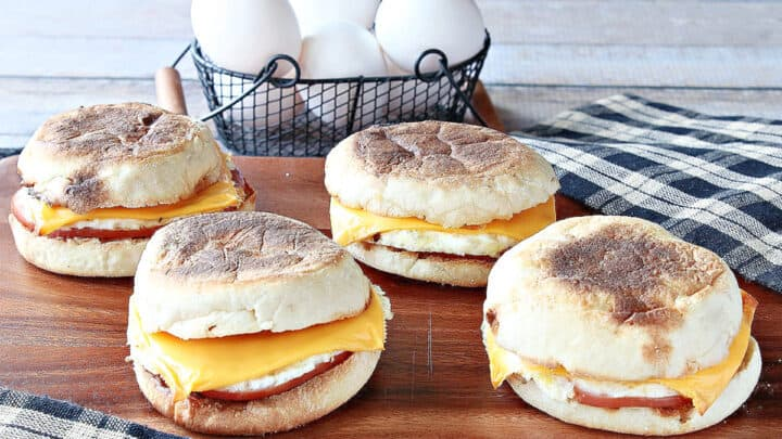 Four Copycat Egg McMuffin Sandwiches on a board with eggs in the background.